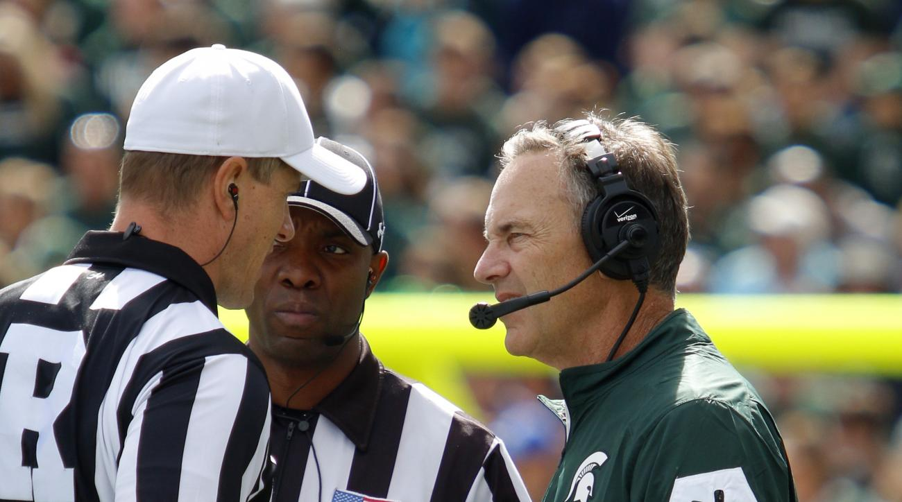 Michigan State coach Mark Dantonio, right, talks to officials Alan Eck, left, and A Flemming during the second quarter of an NCAA college football game against Air Force, Saturday, Sept. 19, 2015, in East Lansing, Mich. Michigan State won 35-21. (AP Photo