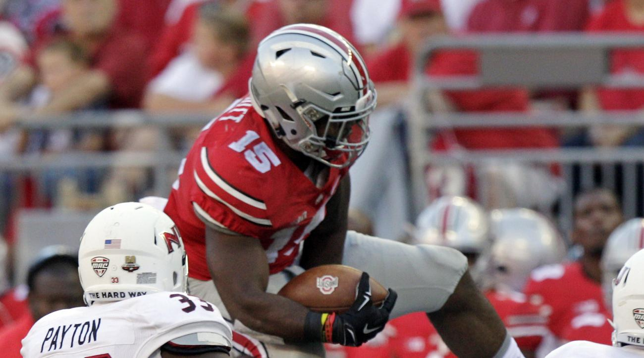 Ohio State running back Ezekiel Elliott, top, leaps over Northern Illinois cornerback Albert Smalls during the third quarter of an NCAA college football game Saturday, Sept. 19, 2015, in Columbus, Ohio. Ohio State won 20-13. (AP Photo/Jay LaPrete)