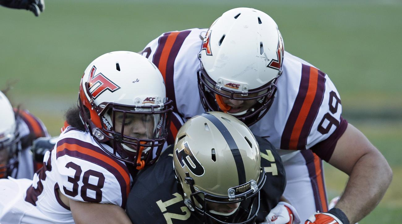 Purdue's Austin Appleby (12) recovers his fumble while being tackled by Virginia Tech's Joe Koshuta (38) and Vinny Mihota (99) during the second half of an NCAA college football game Saturday, Sept. 19, 2015 in West Lafayette, Ind. Virginia Tech won the g