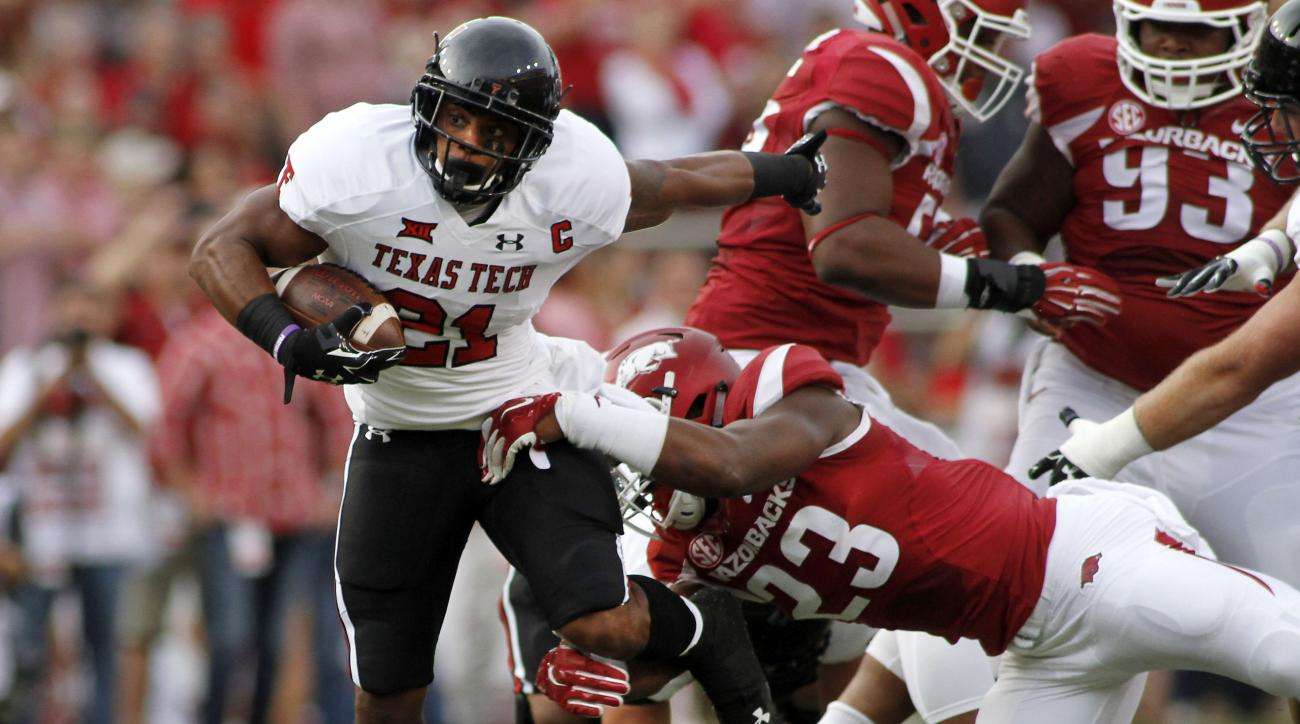 Arkansas' Dre Greenlaw (23) grabs Texas Tech's DeAndre Washington (21) during the first half of an NCAA college football game in Fayetteville, Ark., Saturday, Sept. 19, 2015. (AP Photo/Samantha Baker)