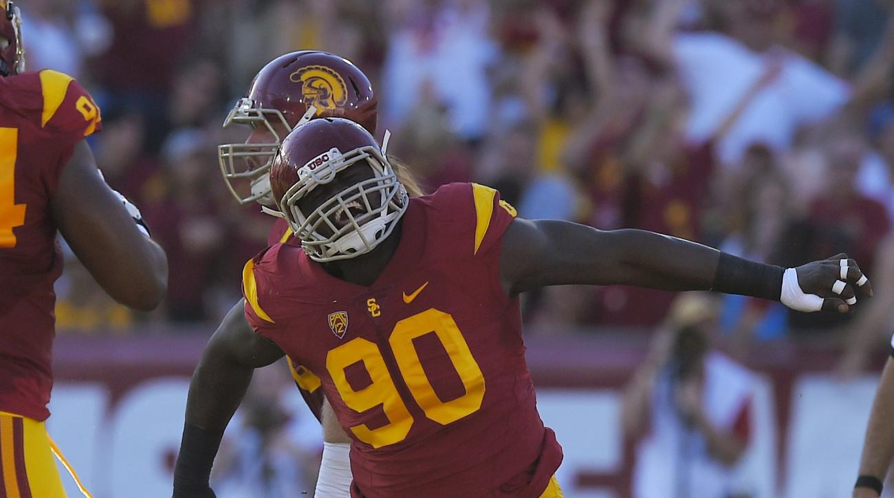 Southern California defensive end Claude Pelon, right, celebrates after Stanford quarterback Kevin Hogan was sacked during the first half of an NCAA college football game, Saturday, Sept. 19, 2015, in Los Angeles. (AP Photo/Mark J. Terrill)