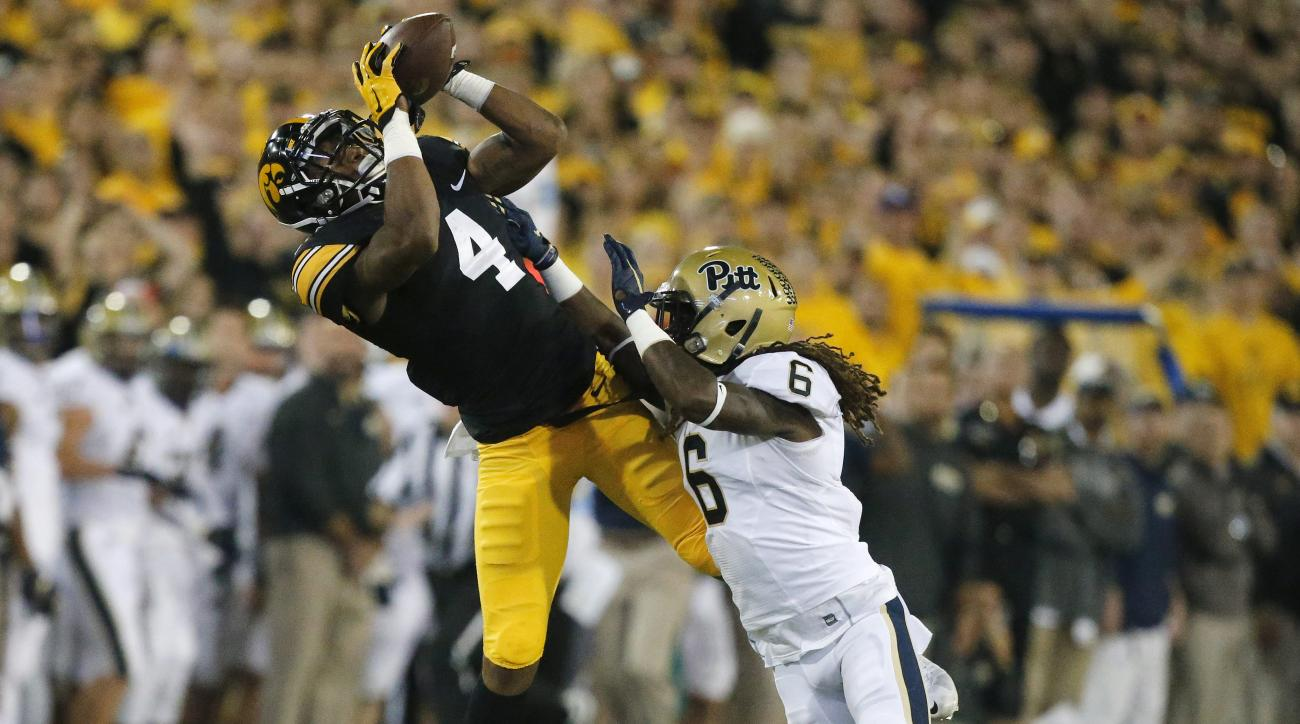 Iowa receiver Tevaun Smith (4) pulls in a catch over Pittsburgh cornerback Lafayette Pitts (6) in the first quarter on Saturday, Sept. 19, 2015, at Kinnick Stadium in Iowa City, Iowa. (Bryon Houlgrave/The Des Moines Register via AP)