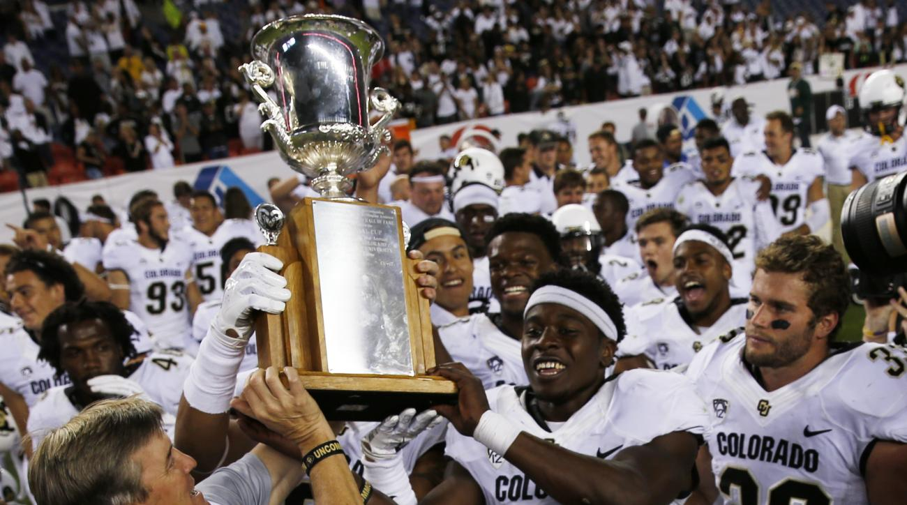 Colorado head coach Mike MacIntyre, front left, hands the Centennial Cup to defensive back Chidobe Awuzie as the rest of the team looks on after defeating Colorado State in the overtime session of an NCAA college football game Saturday, Sept. 19, 2015, in