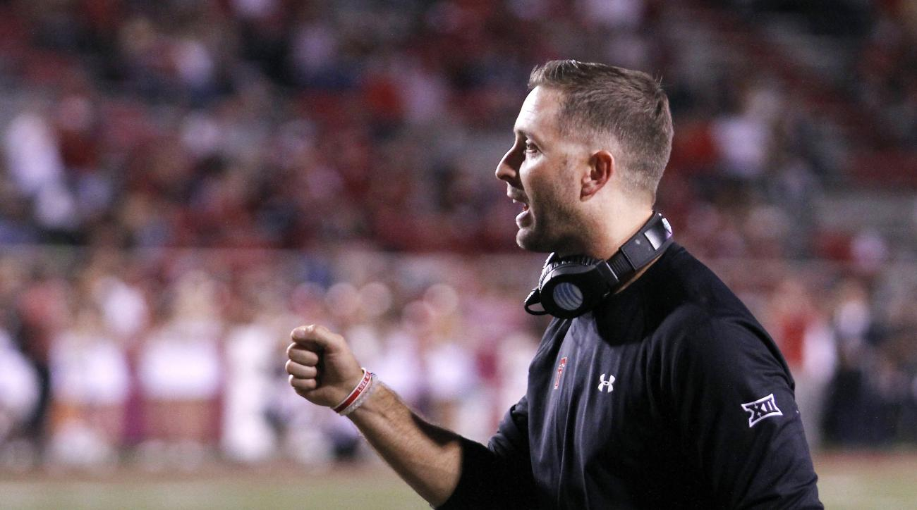 Texas Tech head coach Kliff Kingsbury holds congratulates his players during the second half of an NCAA college football game against Arkansas, Saturday, Sept. 19, 2015, in Fayetteville, Ark. Texas Tech beat Arkansas 35-24. (AP Photo/Samantha Baker)
