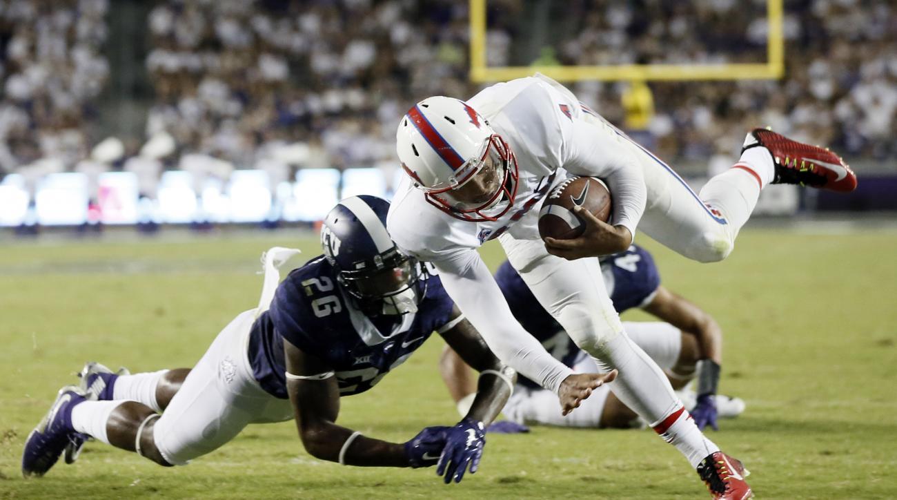 SMU quarterback Matt Davis (4) scores a touchdown against TCU safety Derrick Kindred (26) during the second half of an NCAA college football game Saturday, Sept. 19, 2015, in Fort Worth, Texas. TCU won 56-37. (AP Photo/Tony Gutierrez)