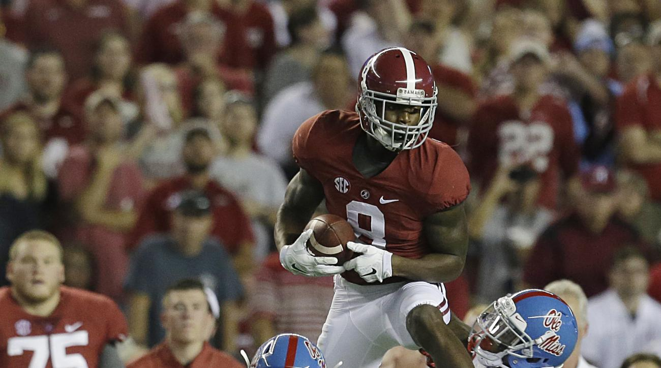 Alabama wide receiver Robert Foster (8) catches the ball against Mississippi linebacker Denzel Nkemdiche (4) and another defender during first half of an NCAA football game, Saturday, Sept. 19, 2015, in Tuscaloosa, Ala. (AP Photo/Butch Dill)