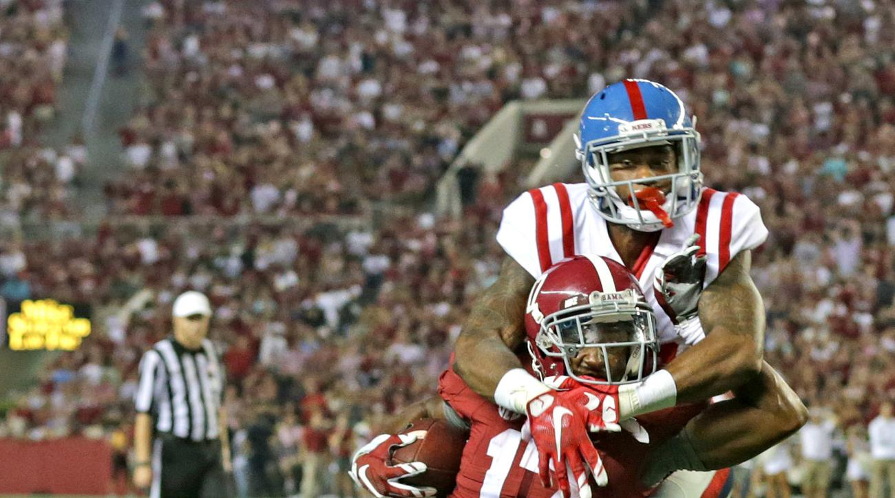 Alabama running back Kenyan Drake, left,  is tackled by Mississippi defensive back Kailo Moore, right, during the second half of an NCAA college football game, Saturday, Sept. 19, 2015, in Tuscaloosa, Ala. (AP Photo/Butch Dill)