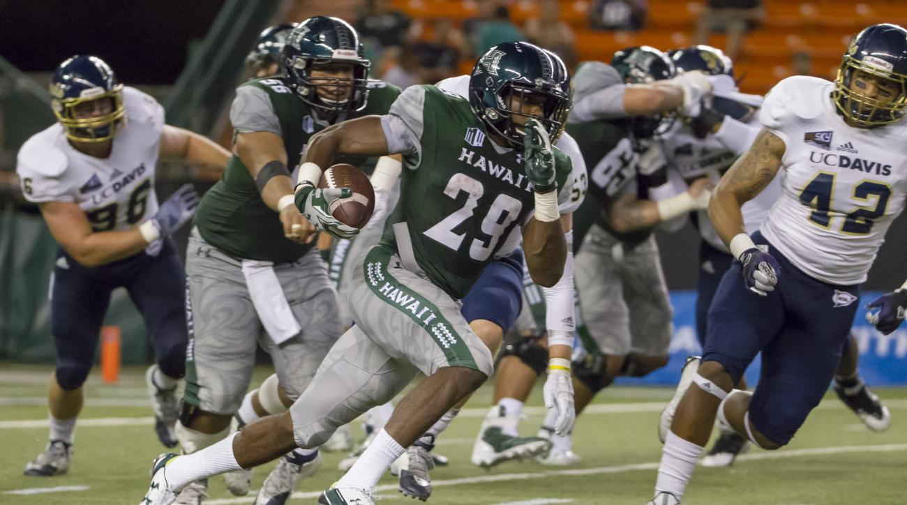 Hawaii running back Paul Harris (29) breaks out of the backfield and runs 98 yards for a touchdown against UC Davis in the third quarter of an NCAA college football game, Saturday, Sept. 19, 2015, in Honolulu. UC Davis linebacker Travon Brooks (42) attemp