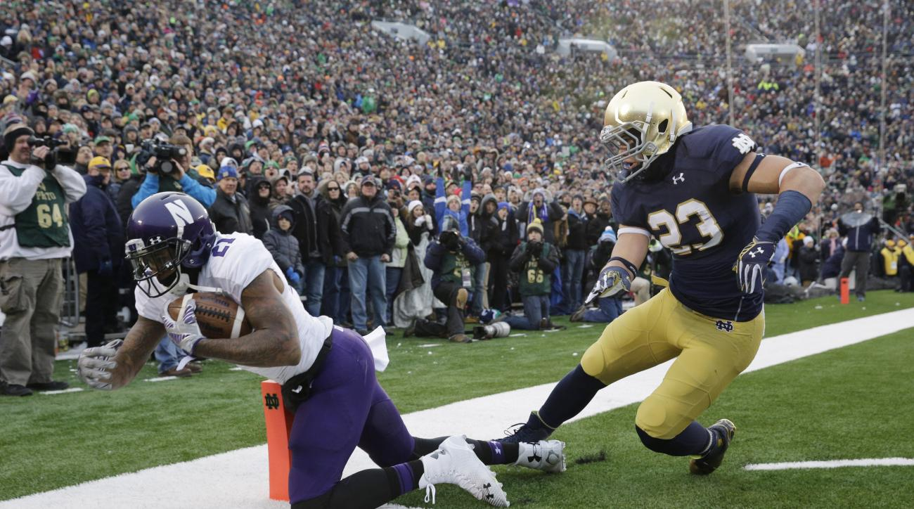 Northwestern wide receiver Kyle Prater (21) catches a touchdown pass against Notre Dame safety Drue Tranquill (23) during the first half of an NCAA college football game in South Bend, Ind., Saturday, Nov. 15, 2014. (AP Photo/Nam Y. Huh)