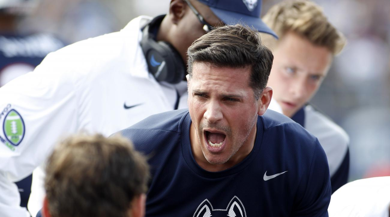 Connecticut head coach Bob Diaco  talks with his players during the second quarter of an NCAA college football game against Navy, Saturday, Sept. 26, 2015, in East Hartford, Conn. (AP Photo/Stew Milne)