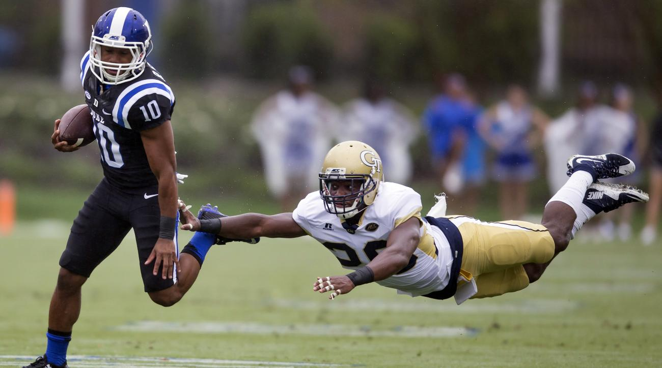Duke's Ryan Smith, left, eludes diving Georgia Tech defender Lawrence Austin during a 68-yard punt return during the first half of an NCAA college football game, in Durham, N.C., Saturday, Sept. 26, 2015. (AP Photo/Rob Brown)