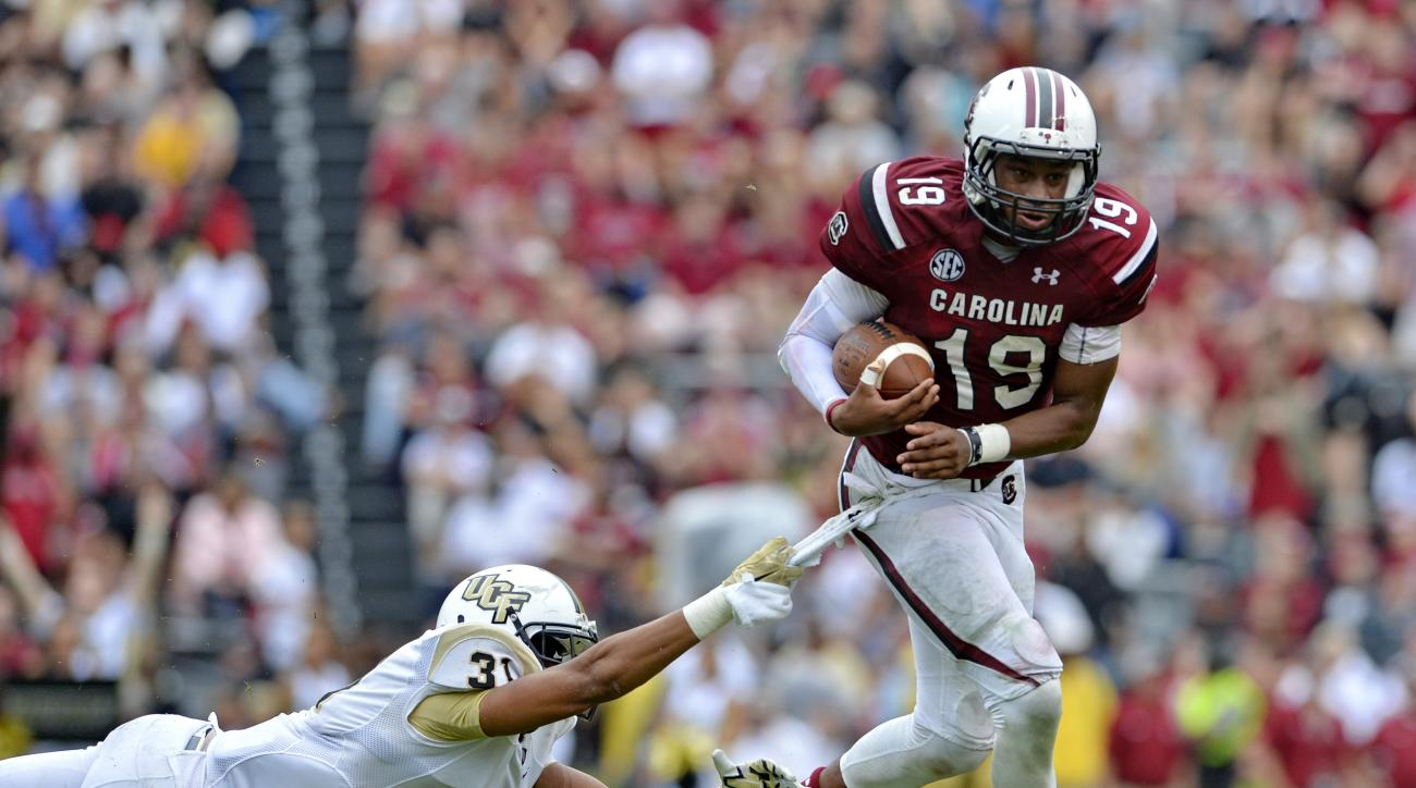 South Carolina quarterback Lorenzo Nunez avoids the tackle attempt by Central Florida's Jeremy Boykins, left, during the second half of an NCAA college football  game Saturday,  Sept. 26, 2015,  in Columbia, S.C. South Carolina won 31-14. (AP Photo/Richar