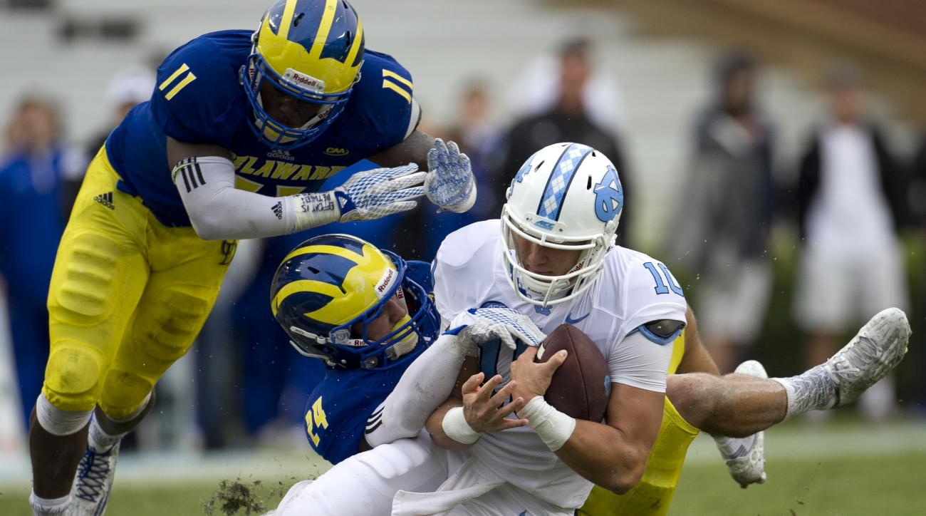 North Carolina quarterback Mitch Trubisky (10) picks up 11 yards before being stopped by Delaware's Ryan Torzsa (24) in the fourth quarter of an NCAA college football game on Saturday, Sept. 26, 2015 at Kenan Stadium in Chapel Hill, N.C. (Robert Willet/Th