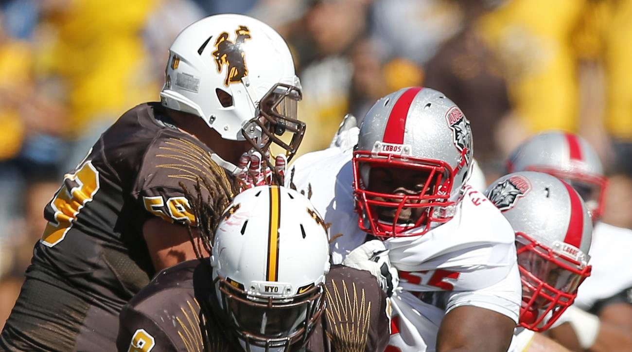 New Mexico's Kimmie Carson (2) and Taylor Timmons (55) tackle Wyoming's Brain Hill (8) during the second quarter of an NCAA college football game, Saturday, Sept. 26, 2015, in Laramie, WY. (AP Photo/Michael Smith)
