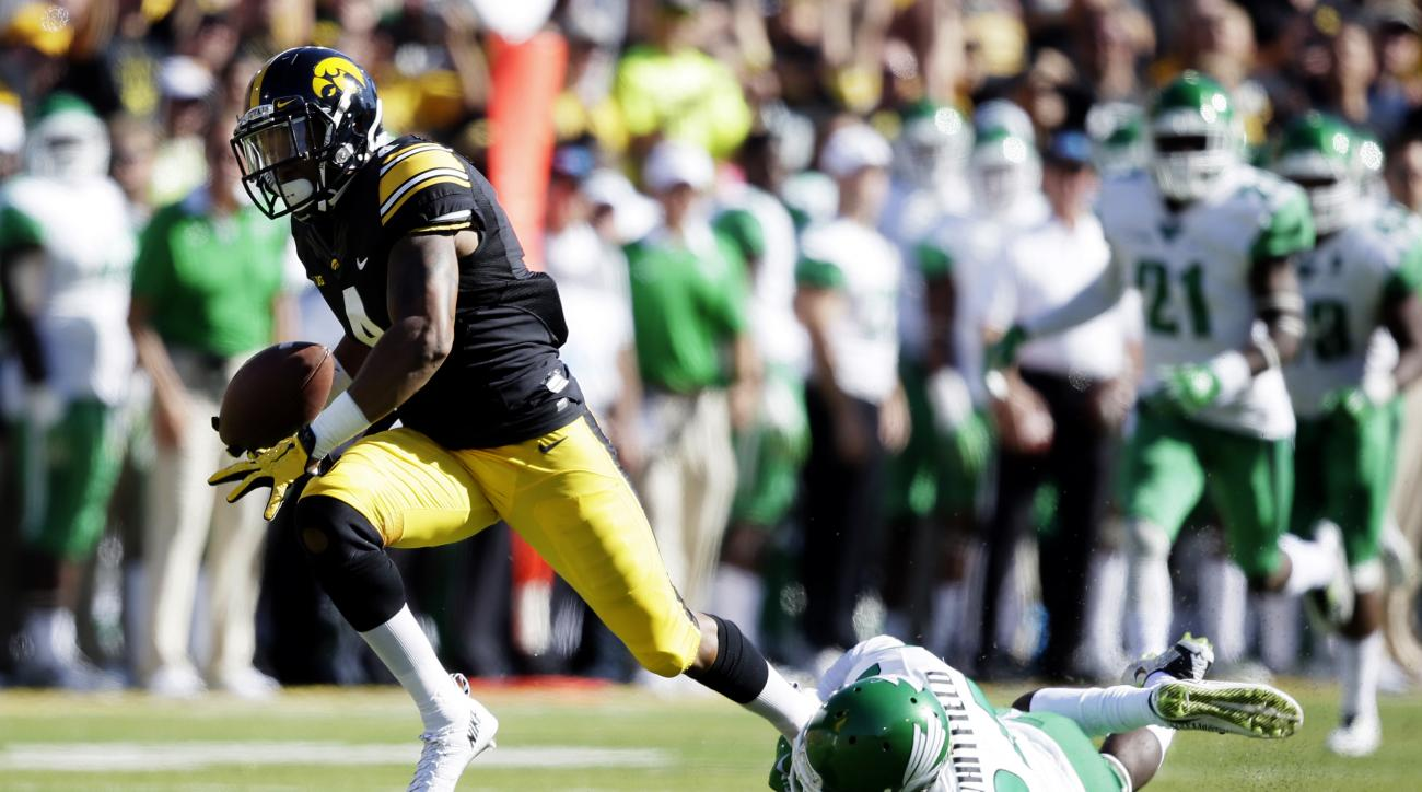 Iowa wide receiver Tevaun Smith breaks a tackle by North Texas defensive back Zac Whitfield, right, during an 81-yard touchdown reception in the first half of an NCAA college football game, Saturday, Sept. 26, 2015, in Iowa City, Iowa. (AP Photo/Charlie N