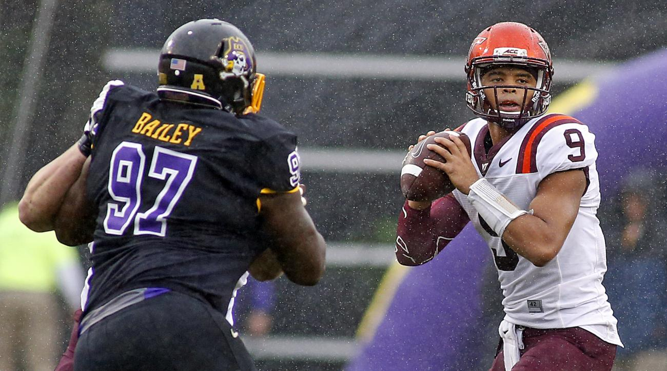 Virginia Tech's Brenden Motley (9) looks to pass the ball as he is hurried by East Carolina's Damage Bailey (97) during the first half of an NCAA college football game in Greenville, N.C., Saturday, Sept. 26, 2015. East Carolina won 35-28. (AP Photo/Karl