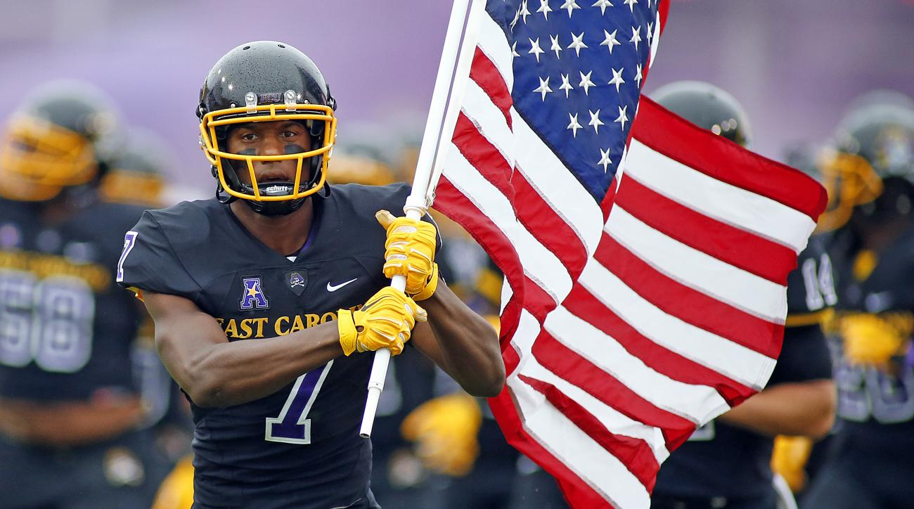 East Carolin's Isaiah Jones (7) enters the field carrying the American Flag prior to the start of their game against Virginia Tech in Greenville, N.C., Saturday, Sept. 26, 2015.  East Carolina won 35-28. (AP Photo/Karl B DeBlaker)