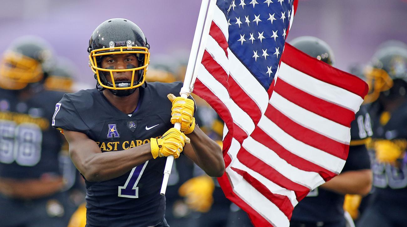 East Carolin's Isaiah Jones (7) enters the field carrying the American Flag prior to the start of their game against Virginia Tech in Greenville, N.C., Saturday, Sept. 26, 2015.  East Carolina won 35-28. (AP Photo/Karl B DeBlaker)