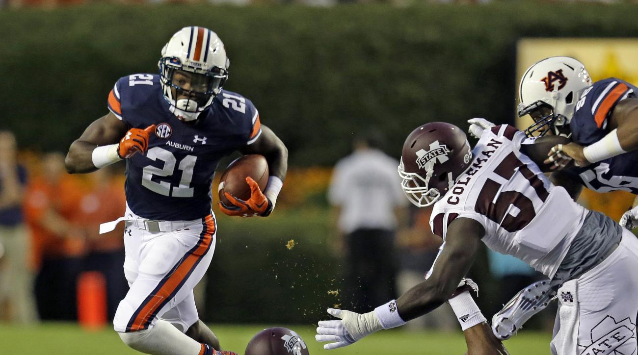 Auburn running back Kerryon Johnson (21) gets around Mississippi State linebacker Zach Jackson (14) and defensive lineman Will Coleman (57) to pick up a first down during the first half of an NCAA college football game, Saturday, Sept. 26, 2015, in Auburn