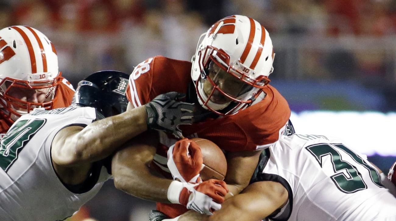 Wisconsin's Taiwan Deal tries to run between Hawaii's Jahlani Tavai (31) and Gaetano DeMattei during the first half of an NCAA college football game Saturday, Sept. 26, 2015, in Madison, Wis. (AP Photo/Morry Gash)