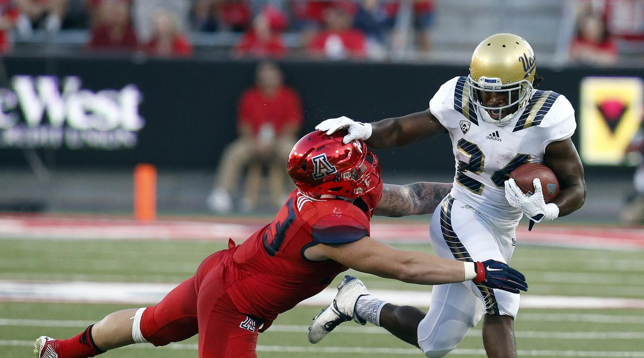 UCLA running back Paul Perkins (24) stiff-arms Arizona linebacker Scooby Wright III during the first half of an NCAA college football game, Saturday, Sept. 26, 2015, in Tucson, Ariz. (AP Photo/Rick Scuteri)