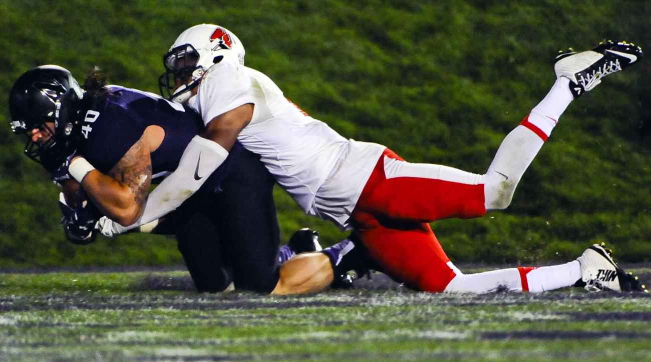 Northwestern fullback Dan Vitale (40) hauls in a touchdown pass while covered by Ball State safety Martez Hester during the third quarter of an NCAA college football game in Evanston, Ill., Saturday, Sept. 26, 2015. (AP Photo/Matt Marton)