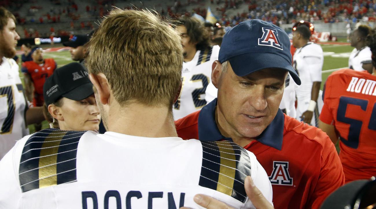 Arizona head coach Rich Rodriguez talks to UCLA quarterback Josh Rosen (3) after an NCAA college football game, Saturday, Sept. 26, 2015, in Tucson, Ariz. UCLA won 56-30. (AP Photo/Rick Scuteri)