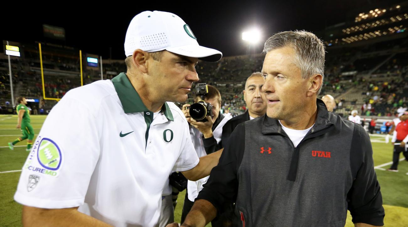 Oregon head coach Mark Helfrich, left, and Utah head coach Larry Krystkowiak, right, shake hands after an NCAA college football game, Saturday, Sept. 26, 2015, in Eugene, Ore. Utah won 62-20. (AP Photo/Ryan Kang)