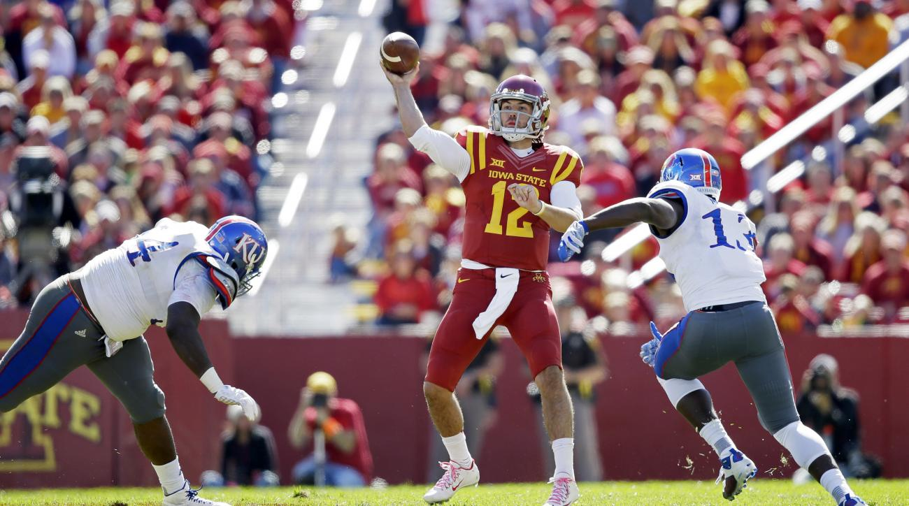 Iowa State quarterback Sam B. Richardson (12) throws a pass between Kansas defenders Jacky Dezir, left, and Damani Mosby, right, during the first half of an NCAA college football game, Saturday, Oct. 3, 2015, in Ames, Iowa. (AP Photo/Charlie Neibergall)