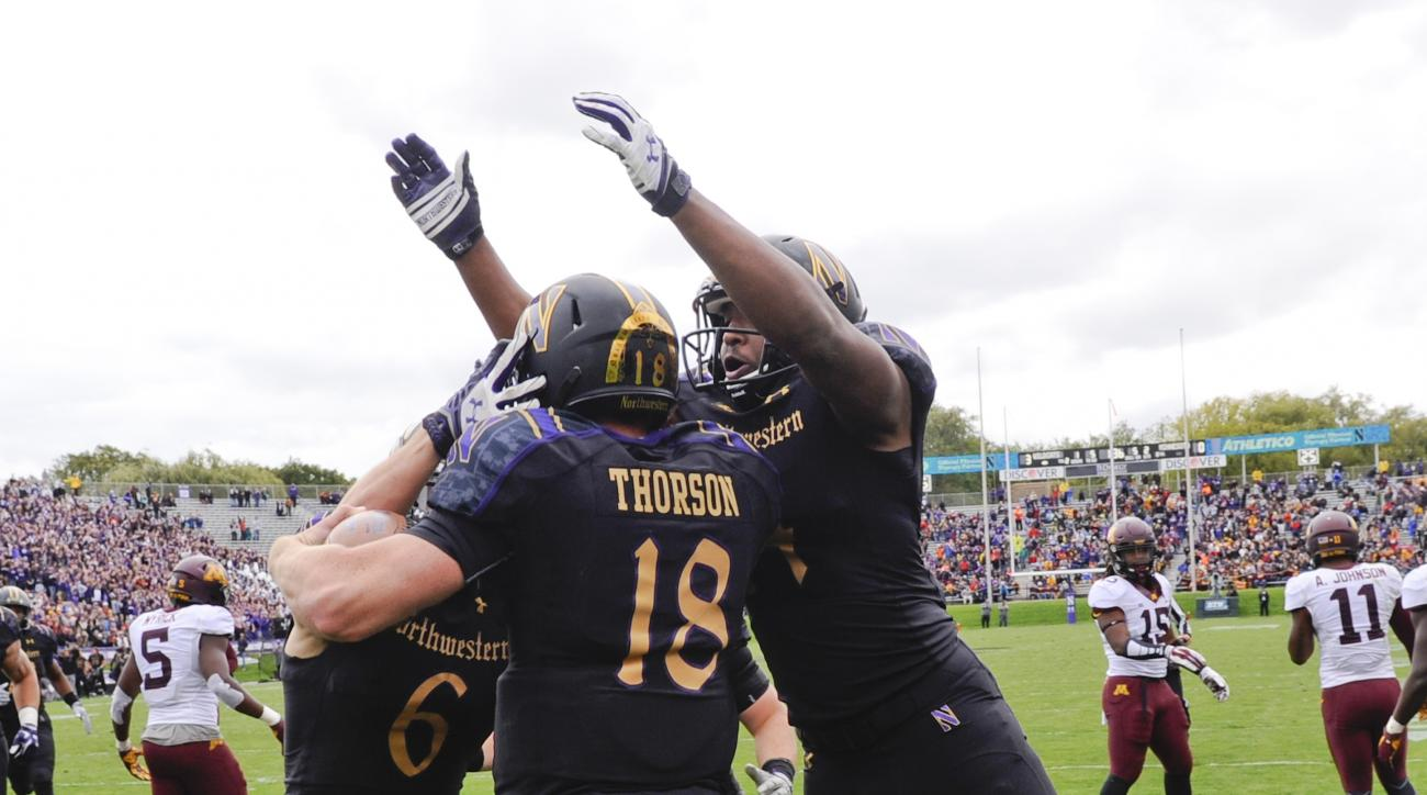 Northwestern quarterback Clayton Thorson (18) celebrates his touchdown run against Minnesota with wide receiver sMike McHugh (6) and Christian Jones, right, during the first half of an NCAA college football game in Evanston, Ill., Saturday, Oct. 3, 2015.