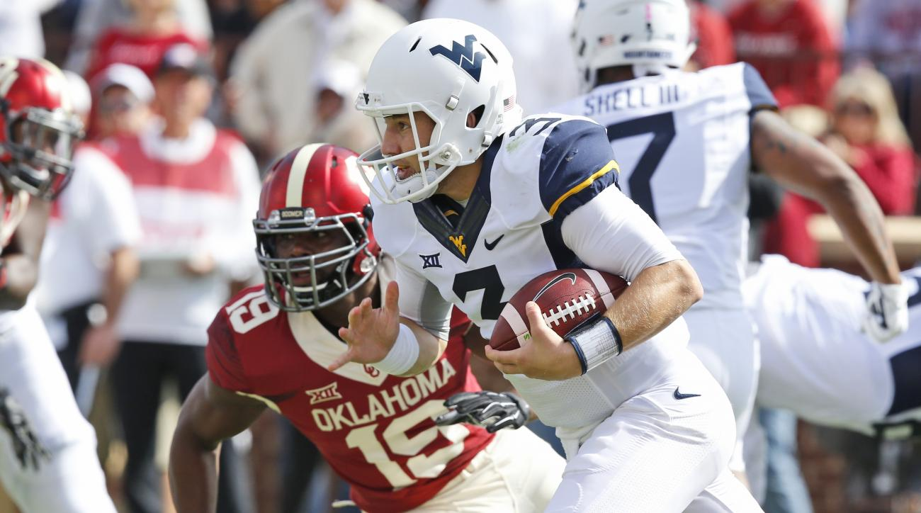 West Virginia quarterback Skyler Howard (3) runs past Oklahoma linebacker Eric Striker (19) in the first quarter of an NCAA college football game in Norman, Okla., Saturday, Oct. 3, 2015. (AP Photo/Sue Ogrocki)