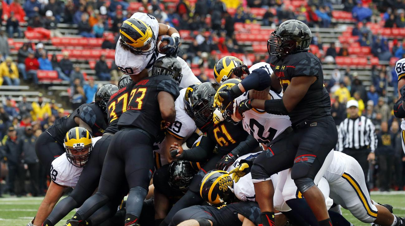 Michigan running back Drake Johnson, top left, leaps into the end zone for a touchdown in the second half of an NCAA college football game against Maryland, Saturday, Oct. 3, 2015, in College Park, Md. Michigan won 28-0. (AP Photo/Patrick Semansky)