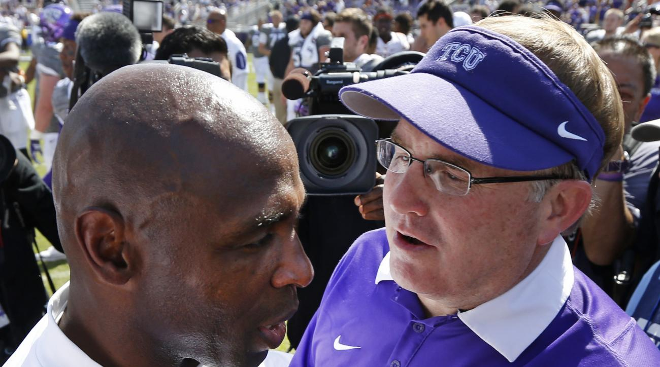 Texas head coach Charlie Strong, left, meets with TCU head coach Gary Patterson, right, after TCU defeated Texas 50-7 in an NCAA football game Saturday, Oct. 3, 2015, in Fort Worth, Texas. (AP Photo/Ron Jenkins)