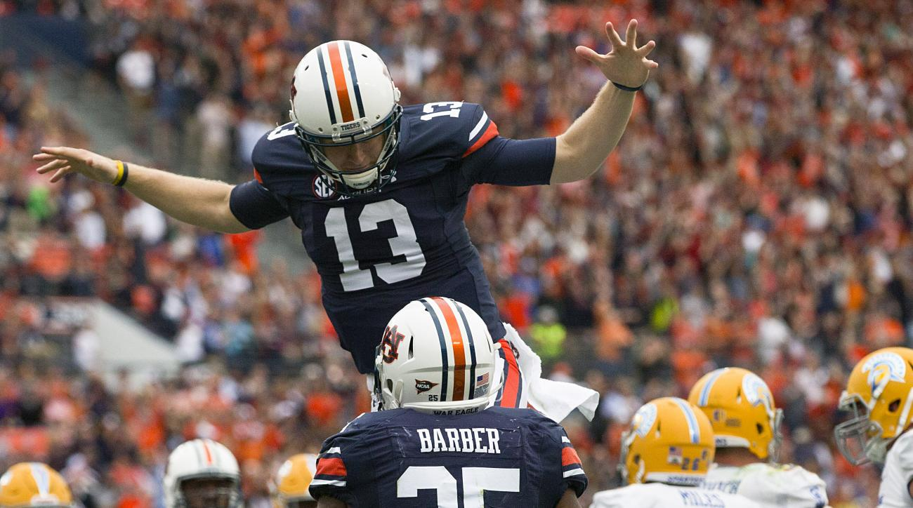 Auburn quarterback Sean White (13) celebrates with Auburn running back Peyton Barber (25) after Barber scored a touchdown during the first half of an NCAA college football game against San Jose State on Saturday, Oct. 3, 2015, in Auburn, Ala. (AP Photo/Br