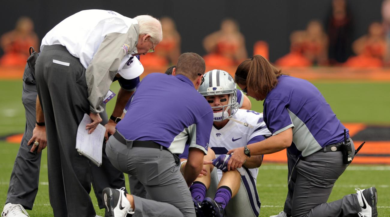 Kansas State head coach Bill Snyder, left, talks with starting quarterback Joe Hubener, center, while medical personnel examine the quarterback during the first quarter of an NCAA football game in Stillwater, Okla.,Saturday, Oct. 3, 2015. (AP Photo/Brody