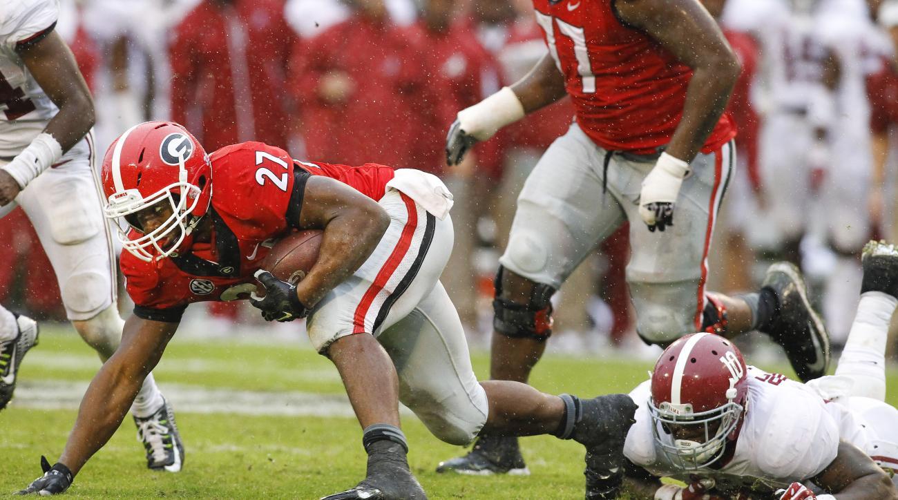 Georgia running back Nick Chubb (27) struggles for extra yardage against Alabama linebacker Reuben Foster (10) in the second half of an NCAA college football game  Saturday, Oct. 3, 2015, in Athens, Ga. Alabama won 38-10. (AP Photo/Brett Davis)