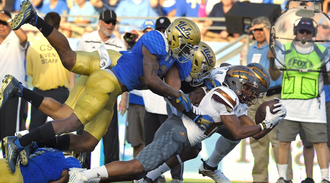 Arizona State wide receiver Tim White, second from right, scores a touchdown under pressure from UCLA defensive back Tahaan Goodman, left, and defensive lineman Sam Tai, second from right, while wide receiver Gary Chambers blocks for White during the firs