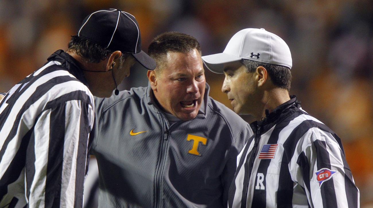 Tennessee head coach Butch Jones argues with referee Marc Curles, right, as head linesman John Langlois listens during the second half of an NCAA college football game against Arkansas Saturday, Oct. 3, 2015 in Knoxville, Tenn. Arkansas won 24-20. (AP Pho