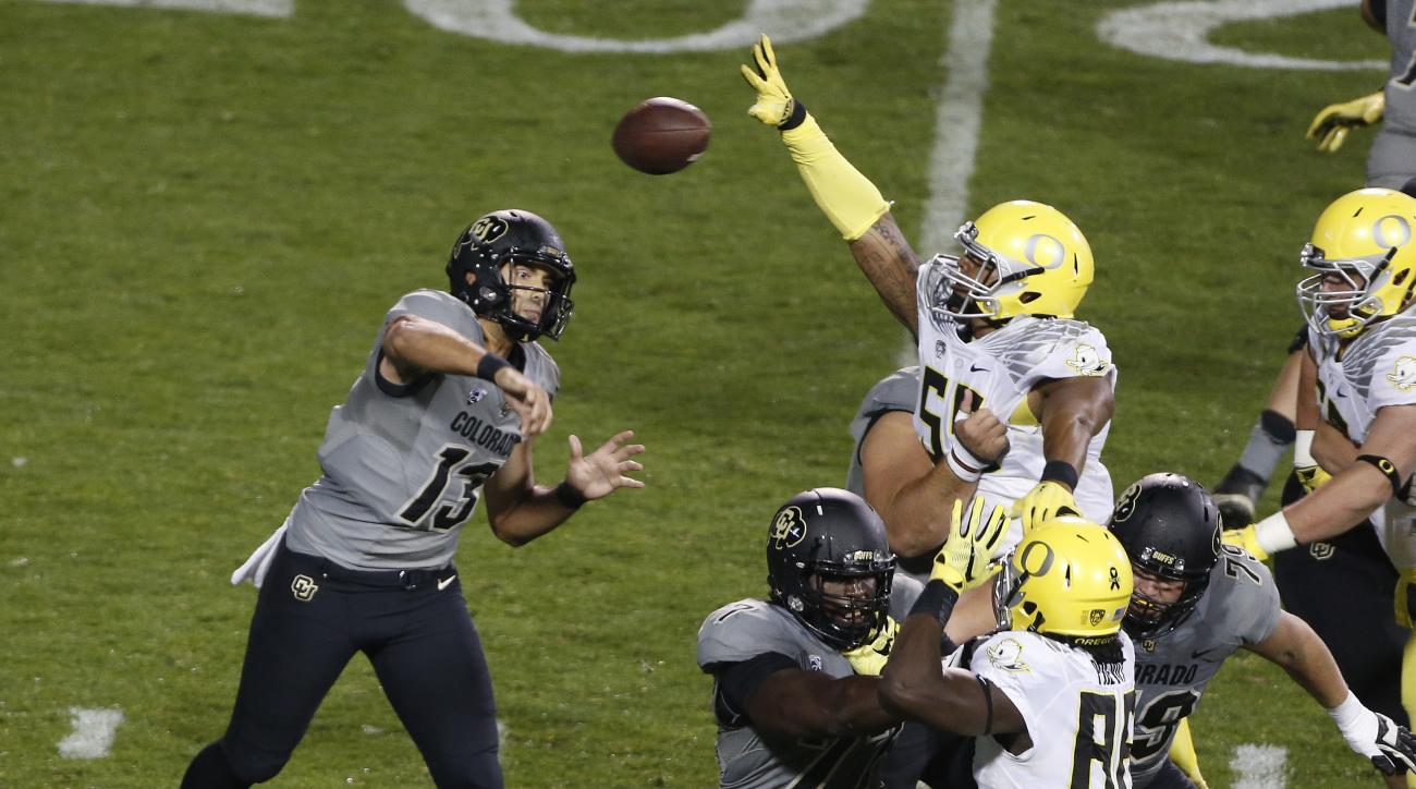 Colorado quarterback Sefo Liufau (13) throws past an attempted block by Oregon's defense in first half of an NCAA college football game in Boulder, Colo., Saturday, Oct. 3, 2015. (AP Photo/Brennan Linsley)