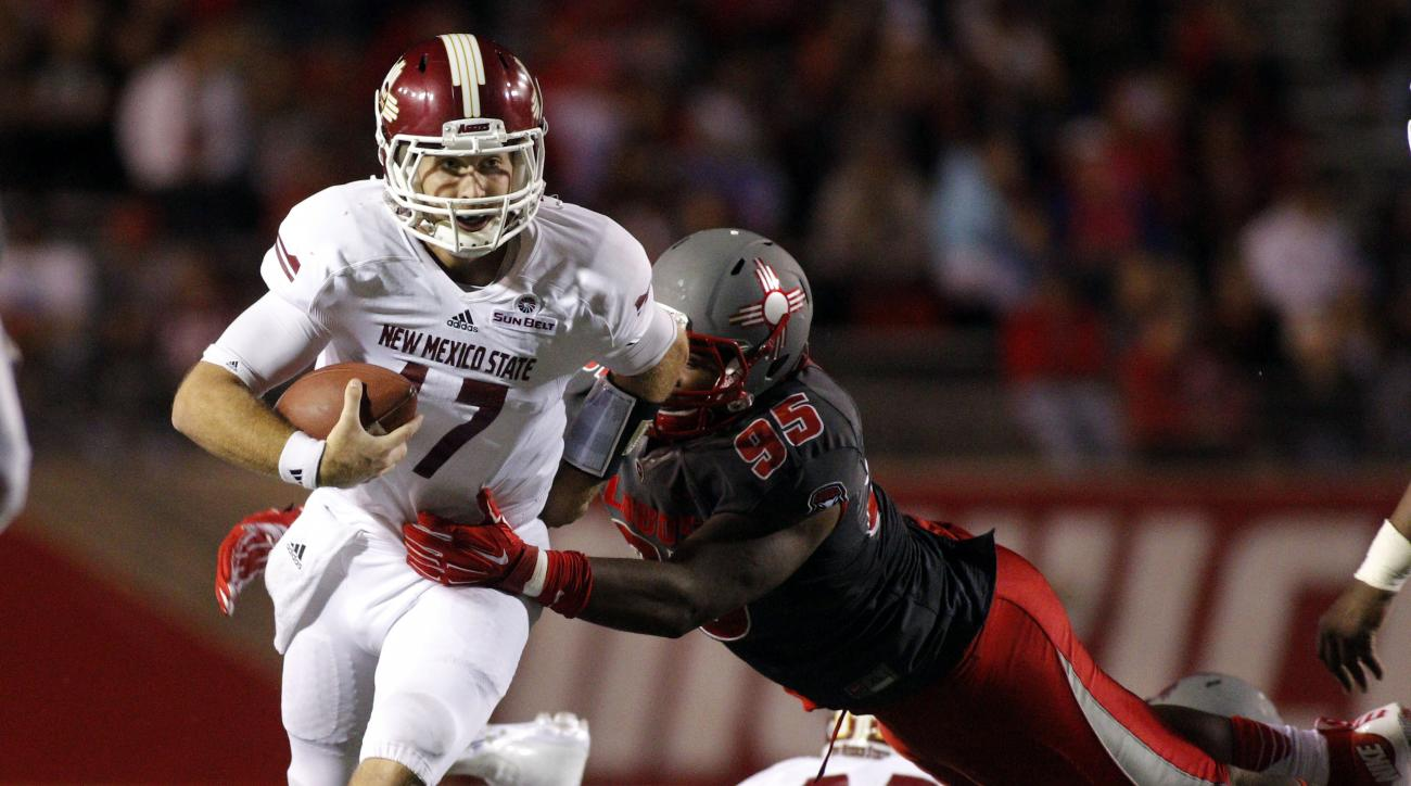 New Mexico State quarterback Tyler Rogers, left, is tackled by New Mexico defensive lineman Garrett Hughes during the second half of an NCAA college football game in Albuquerque, N.M., Saturday, Oct. 3, 2015. New Mexico won 38-29. (AP Photo/Andres Leighto
