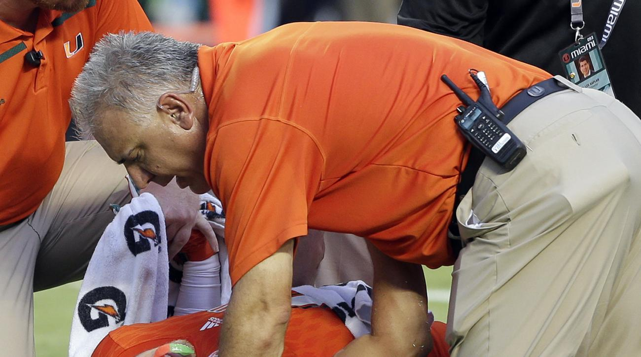 FILE - In this Sept. 2, 2015, file photo, Miami wide receiver Braxton Berrios (8) grimaces in pain after an injury in the first half of an NCAA college football game against Bethune Cookman in Miami Gardens, Fla. ACC Commissioner John Swofford embraced an