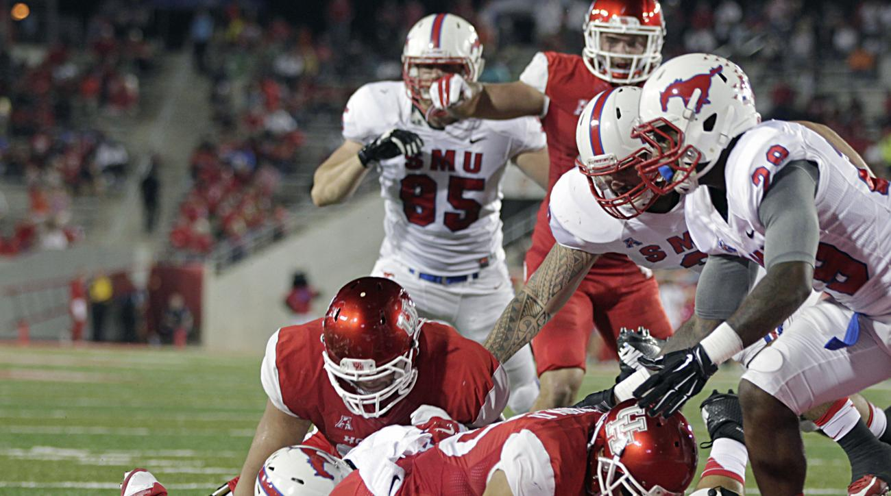 Houston running back Kenneth Farrow dives past SMU defenders for a touchdown during the first half of an NCAA college football game Thursday, Oct. 8, 2015, in Houston. (James Nielsen/Houston Chronicle via AP) MANDATORY CREDIT