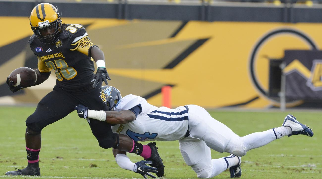 Kennesaw State running back Darnell Holland (33) is hit by Point cornerback Kalen Newsome (4 ) during the first half of an NCAA college football game, Saturday, Oct. 10, 2015, in Kennesaw, Ga. (AP Photo/Lisa Marie Pane)