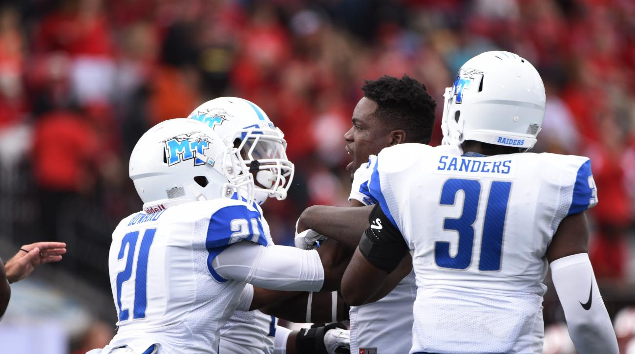 Middle Tennessee defensive end Alexandro Antoine (17) is held back my teammates as he argues with Western Kentucky players during the first half an NCAA college football game on Saturday, Oct. 10, 2015, at L.T. Smith Stadium in Bowling Green, Ky. (AP Phot