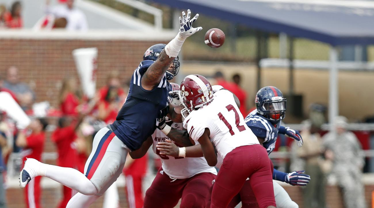 Mississippi defensive tackle Robert Nkemdiche (5) stretches as he tries to block a pass from New Mexico State quarterback Nick Jeanty (12) in the second half of an NCAA college football game in Oxford, Miss., Saturday, Oct. 10, 2015.  Mississippi won 52-3