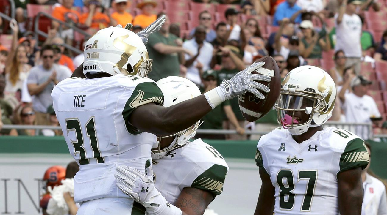South Florida running back Darius Tice (31) celebrates his one-yard touchdown run with teammates tight end Sean Price (12) and wide receiver Rodney Adams (87) during the second quarter of an NCAA college football game against Syracuse Saturday, Oct. 10, 2