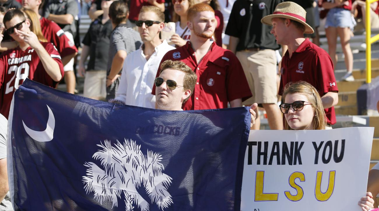 Fans hold a signs in support of South Carolina during the first half of an NCAA college football game between LSU and South Carolina in Baton Rouge, La., Saturday, Oct. 10, 2015. The game was moved from Columbia, S.C. to Baton Rouge because of flooding. (