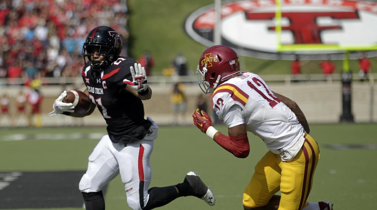 Texas Tech's DeAndre Washington carries the ball as Iowa State's Jarnor Jones defends during an NCAA college football game, Saturday, Oct. 10, 2015, in Lubbock, Texas. (Mark Rogers/Lubbock Avalanche-Journal via AP)