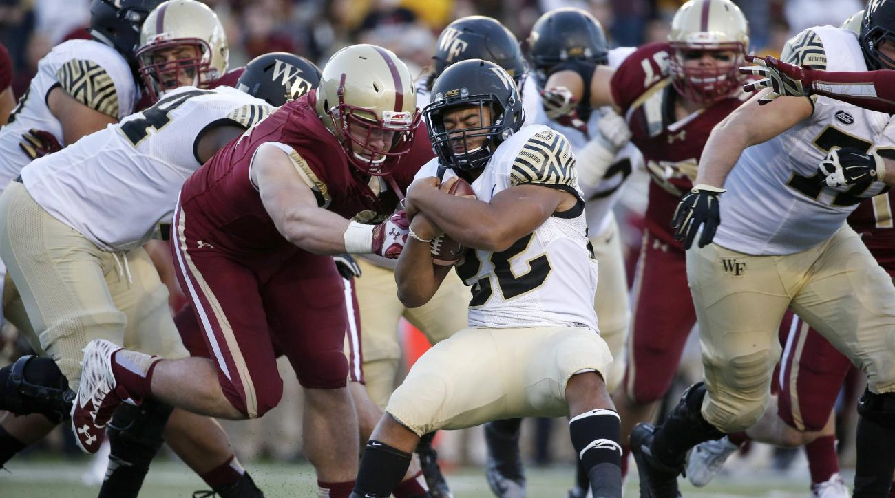Boston College defensive end Kevin Kavalec, center left, stops Wake Forest running back Matt Colburn (22) during the fourth quarter of an NCAA college football game in Boston, Saturday, Oct. 10, 2015. Wake Forest won 3-0. (AP Photo/Michael Dwyer)