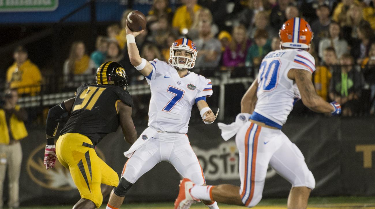 Florida quarterback Will Grier, center, throws a pass over Missouri's Charles Harris, left, to DeAndre Goolsby, right, during the first half of an NCAA college football game, Saturday, Oct. 10 2015, in Columbia, Mo. (AP Photo/L.G. Patterson)